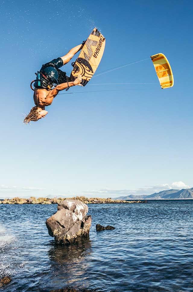 Kitesurfer jumping over stone